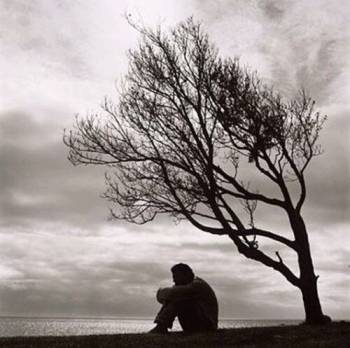 Sad man sitting under a tree